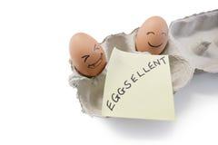 """Smileygezichten op eieren met """"eggsellent"""" op schrijfpapier worden geschreven dat stock foto"""