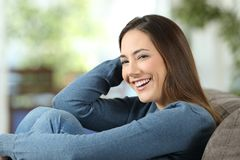 Smileyhemmafru som hemma poserar på en soffa Royaltyfri Bild