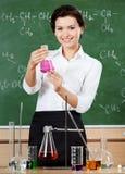 Smileykemilärare hands en Erlenmeyer flaska royaltyfri bild