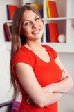 Kvinna som poserar över bokhylla Royaltyfri Bild