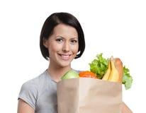 Smileymädchen hält das Paket des Gemüses Stockfotos