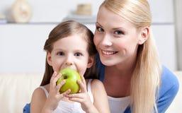 Smileymamma mit ihrer essenden Apfeltochter Lizenzfreies Stockbild