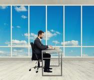 Smileymann, der im hellen Büro arbeitet Lizenzfreie Stockfotos
