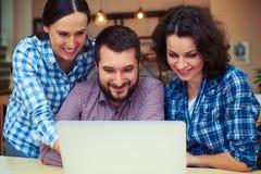Smileymann und -frauen, die mit Laptop arbeiten Lizenzfreie Stockfotografie