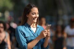 Smileymeisje die een slimme telefoon met behulp van die in de straat lopen royalty-vrije stock foto