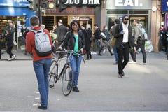 Smileymeisje in een groene t-shirt die de weg op een fiets kruisen Stock Foto's