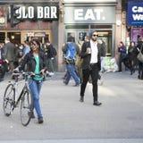 Smileymeisje in een groene t-shirt die de weg op een fiets kruisen Stock Fotografie