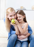 Smileymoder med henne som äter äppledottern royaltyfria bilder