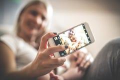 Smileymutter mit ihrem Baby zu Hause, das Selbstporträt nimmt stockfoto