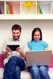 Paare, die auf Sofa sitzen und Computer halten Stockfotos