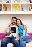 Verbinden Sie das Sitzen auf Sofa und das Halten des Tablette-PC Lizenzfreie Stockfotos