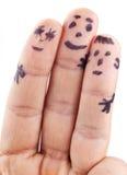 Smileys av familjen som målas på mans fingrar Arkivbild