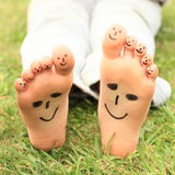 Smileys on toes and soles. Kids bare feet with funny ten smileys on toes and two on soles Royalty Free Stock Photos