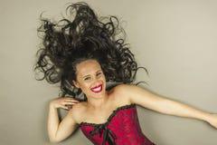 Smileyschönheit mit dem langen Haar und rotes Korsett legen nieder stockfotos
