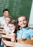 Smileyschoolgirlen sitter på skrivbordet Arkivfoto