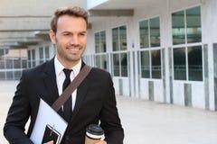 Smileyzakenman die buiten het bureaugebouw lopen Royalty-vrije Stock Fotografie
