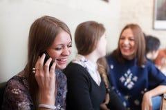 Smilie девушки пока говорящ на сотовом телефоне в кофейне Стоковая Фотография