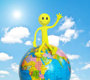 Smilie sitting on the globe Royalty Free Stock Image