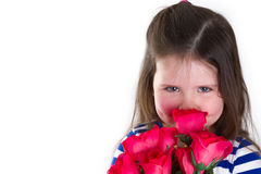 Smilie. Young girl holding a bunch of artifical roses smelling them. Looking at the camera and lots of copy space Stock Photography