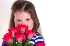 Smilie. Young girl holding a bunch of artifical roses smelling them. Looking at the camera and lots of copy space Royalty Free Stock Image