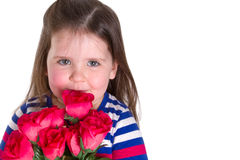Smilie. Young girl holding a bunch of artifical roses smelling them. Looking at the camera and lots of copy space Royalty Free Stock Photo