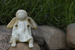 Smilig angel with pigtails. Sitting on rock, surrounded by lavender Royalty Free Stock Photos