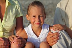 Smiliing daughter sitting between parents on beach. Summer Royalty Free Stock Photos
