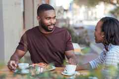 Smiliing young African couple talking together at a sidewalk cafe. Smiling young African couple sitting at a table at a sidewwalk cafe drinking coffee and Royalty Free Stock Photos