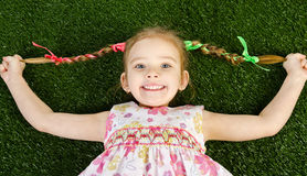 Smililing happy little girl lying on grass. And holding her braids royalty free stock photos