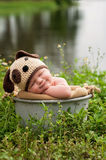 Smililng Baby Boy Wearing a Puppy Dog Hat. A smiling three month old baby boy wearing a crocheted puppy dog hat. He's sleeping in a galvanized steel bucket that' Stock Image