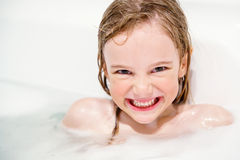 Smililng girl in bath. A happy, smiling girl in a white bath Royalty Free Stock Photo