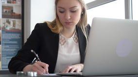 Smilimg arbetar den blonda flickan på datoren, genom att använda hennes bärbar dator Hon är märkes- Självständig arkitekt för ung lager videofilmer