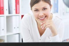 Smilimg asiatique de sourire de femme d'affaires de jeunes in camera tout en travaillant sur un ordinateur portable photos stock
