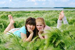 Smilimg girls lie on the bank of lake Stock Photo