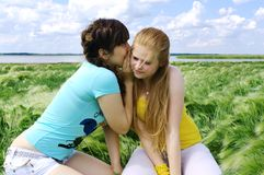 Smilimg girls lie on the bank of lake Royalty Free Stock Photo