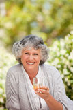 Smilimg woman with her drink of wine Stock Photo