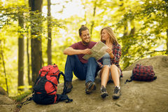 Smilimg young couple seating on the rock in the forest Royalty Free Stock Image