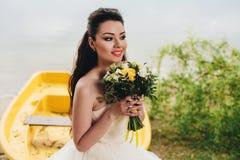 Smilind de la novia y el sentarse en el barco Fotos de archivo