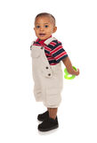 Smiling 1-year old baby boy standing holding toy Stock Image