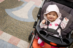 Smiling 5 month old Chinese baby girl. Sitting in her stroller Royalty Free Stock Photography