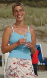 Smiling. Young woman with a glass of wine on the beach of the island Sylt, germany Royalty Free Stock Photo