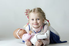 Smiling. Young Girl lying on floor with doll in arms Stock Photos