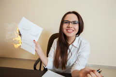 Smiling accountant burns financial documents Stock Images