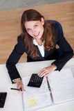 Smiling accountant sitting at her desk working Stock Image