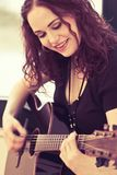 Smiling acoustic guitar player Stock Photos