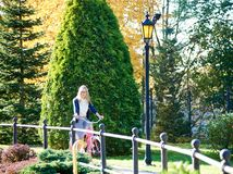 Blond long-haired attractive girl on pink lady bicycle in sunny autumn park on trees background. Smiling active blond long-haired attractive traveler woman in Stock Image