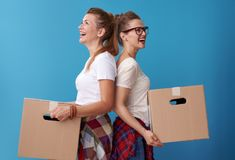 Female roommates with a cardboard boxes standing back to back Stock Image