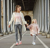 Smiling active mother and child on bridge in Paris going forward Stock Photography