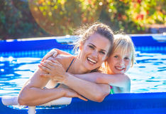 Smiling active mother and child in swimming pool embracing. Fun weekend alfresco. Portrait of smiling active mother and child in swimwear in the swimming pool Stock Images