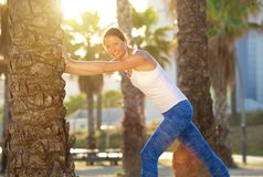 Smiling active woman stretching leg muscles outside Stock Photo